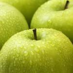 Närbild av gröna äpplen med regndroppar