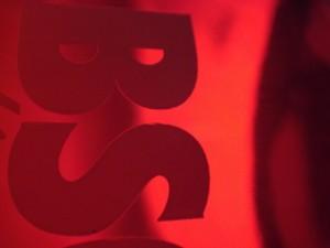 närbild på en flaska där bokstäverna BS syns, med rött ljus i bakgrunden