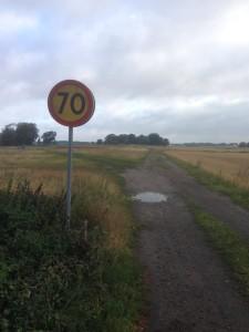 Horisontbild över åker med en vägskylt som visar 70 till vänster i bilden