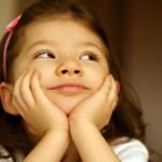 barn som sitter med ansiktet i händerna tittar uppåt och tänker