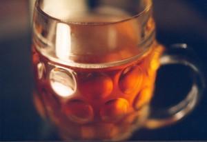 En sejdel med mörkt öl i närbild, svart bakgrund