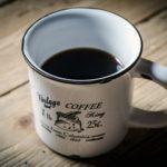 en vit kopp med svart kaffe i närbild