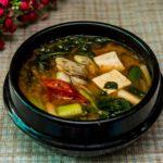 en svart skål med soppa på buljong med grönsaker och tofu i