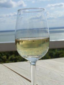 Ett glas vitt vin på ett bord med havet i bakgrunden